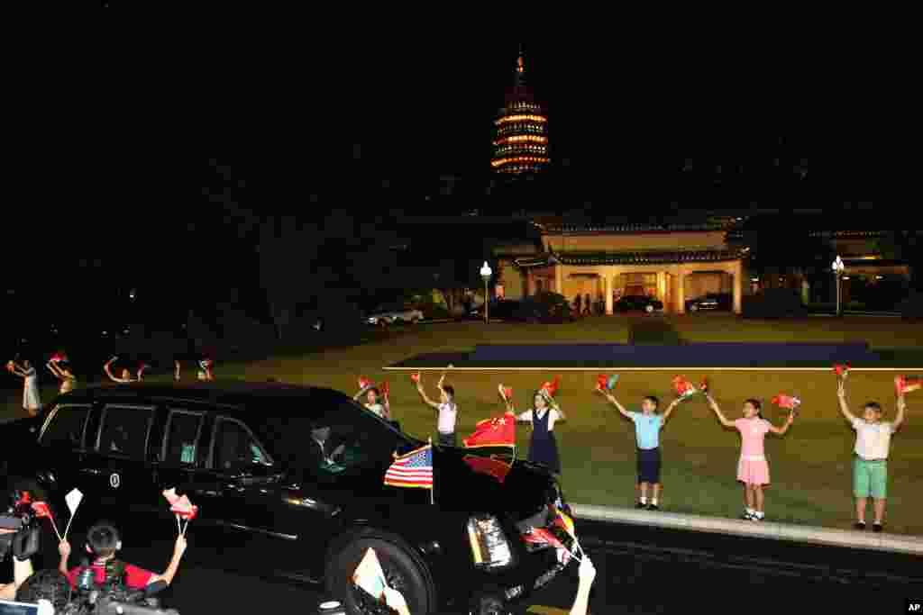 在美国总统奥巴马的大轿车驶过的时候,中国儿童举着两国国旗列队欢迎(2016年9月4日)