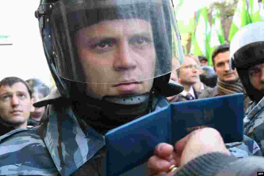 Народный депутат Андрей Кожемякин безуспешно пытается пройти сквозь заслон, показывая бойцу спецподразделения «Беркут» свое депутатское удостоверение