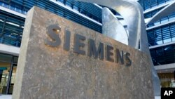 FILE -The logo of German industrial conglomerate Siemens is pictured at the headquarters in Munich, Germany.