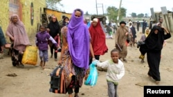 Somali families move out of their homes after they were broken into during the second day of skirmishes in the Eastleigh neighborhood of Kenya's capital Nairobi, Nov. 19, 2012.