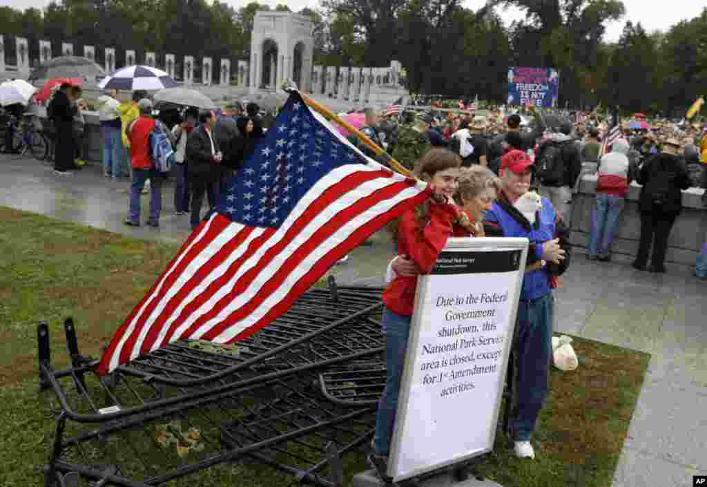 Kaylee, Sherry and Michael Cantrell pose for a photo with a sign and removed barricades at the World War II Memorial in Washington, Oct. 13, 2013.