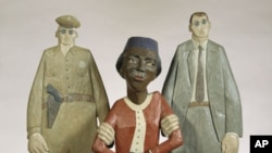 In this wooden sculpture by Marshall D. Rumbaugh, Rosa Parks is held by two policemen. Parks was arrested after refusing to give up her seat to a white male bus rider in Montgomery, Alabama.