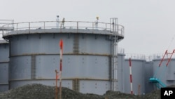 FILE - Workers wearing protective gears stand on the water tank that stores contaminated water at the Fukushima Dai-ichi nuclear power plant in Okuma, Fukushima prefecture, northeastern Japan, Nov. 12, 2014.
