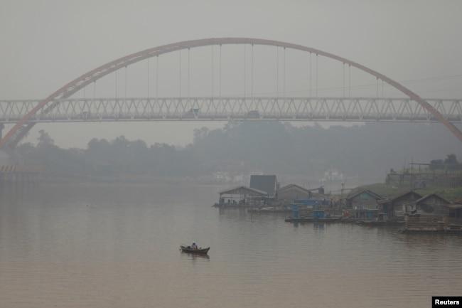 Seorang pria memancing saat kabut asap menutupi sungai Kahayan di Palangka Raya, Provinsi Kalimantan Tengah, 17 September 2019. (Foto: REUTERS/Willy Kurniawan)
