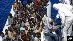 지난 22일 지중해에서 이탈리아의 구조용 고무보트에 탄 난민들이 이탈리아 해안경비선으로 옮겨타고 있다. (자료사진)