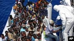 Migrants crowded in an inflatable dinghy await rescue by the Italian coast guard's vessel Denaro off the Libyan coast, in the Mediterranean Sea, April 22, 2015.