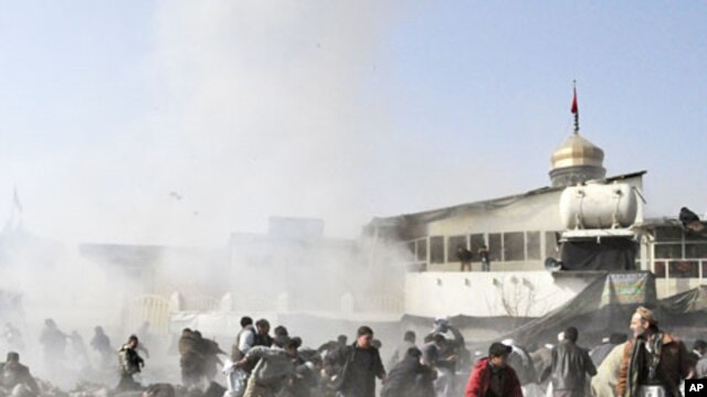 People react seconds after a suicide blast targeting a Shi'ite Muslim gathering in Kabul, December 6, 2011.