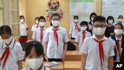 ویتنام کے شہر ہنوئی میں ماسک پہنے بچے قومی ترانہ پڑھ رہے ہیں
