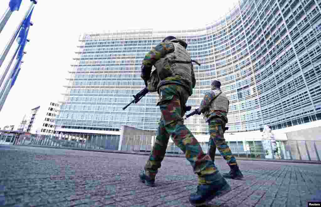 Belgian soldiers patrol outside the European Commission headquarters as police searched the area during a continued high level of security following the recent deadly Paris attacks, in Brussels.