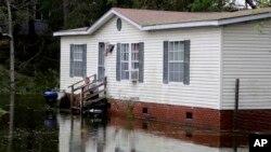 Joe Wiggins sjedi na trijemu svoje kuće dok ga okružuje voda nakon što je uragan Florence protutnjao ostrvom Emerald, Sjeverna Karolina, 16. septembra 2018.