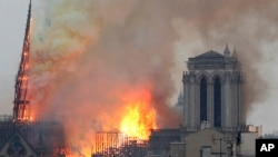 Flames rise from Notre Dame cathedral as it burns in Paris, Monday, April 15, 2019. Massive plumes of yellow brown smoke is filling the air above Notre Dame Cathedral and ash is falling on tourists and others around the island that marks the center of Par