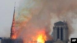 Flanm difi k ap monte sou tèt Katedral Notre Dame nan vil Pari lendi 15 avril 2019 la. Gwo lafimen jonn-mawon ap ranpli lè a sou tèt building nan tandiske sanndife ap tonbe sou touris ak lot moun ki rasanble alantou katedral la, youn nan pi gwo sanbòl vil Pari yo.