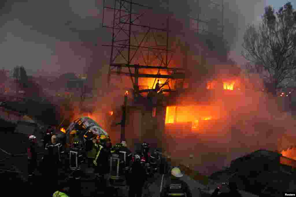 Firefighters try to extinguish a fire caused by the explosion of a gas tanker truck in San Pedro Xalostoc, Mexico, May 7, 2013.