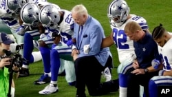 The Dallas Cowboys, led by owner Jerry Jones, center, take a knee before the national anthem at an NFL football game against the Arizona Cardinals, in Glendale, Ariz., Sept. 25, 2017.