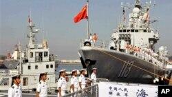 中国海军官兵准备登上青岛号导弹驱逐舰(右)去参加中美海军联合演习(2013年8月20日)