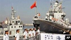 中国海军官兵登上青岛号导弹驱逐舰(右)去参加中美海军联合演习