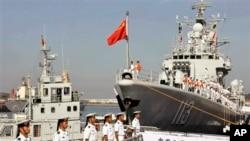 中国海军官兵登上青岛号导弹驱逐舰(右)去参加2013年9月中美海军联合演习。