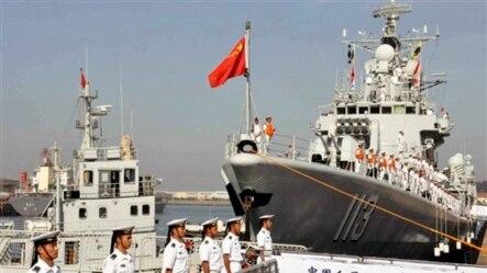 中国海军官兵站在青岛号导弹驱逐舰上(右)准备去参加中美海军联合演习(2013年8月20日)