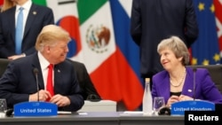 FILE - U.S. President Donald Trump and Britain's Prime Minister Theresa May attend the G20 leaders summit in Buenos Aires, Argentina, Nov. 30, 2018.