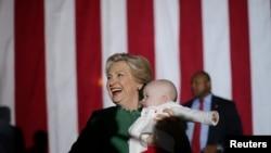 힐러리 클린턴 민주당 대통령 후보가 23일 노스캐롤라이나주 샬럿 유세에서 아기를 안은 채 웃음짓고 있다.