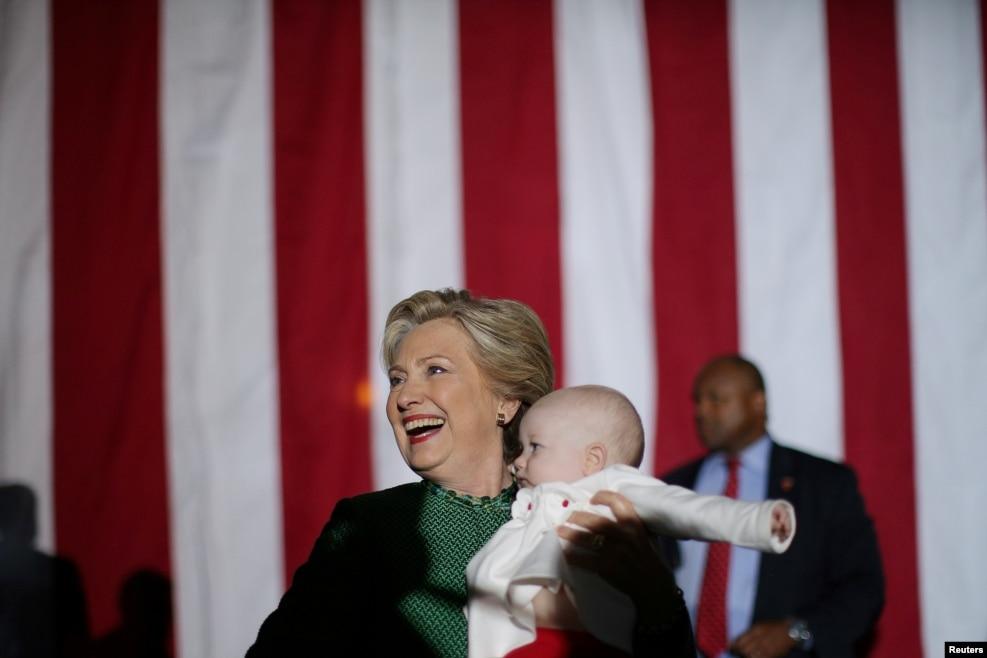 2016年10月23日,克林顿在北卡罗莱纳州参加竞选活动后抱着一个婴儿