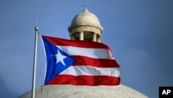 FILE - The Puerto Rican flag flies in front of the U.S. territory's Capitol in San Juan, Puerto Rico, July 29, 2015.