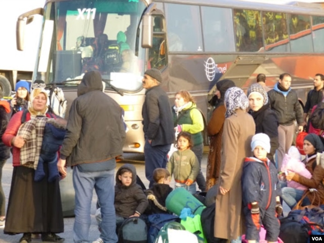 New arrivals are transferred by bus to other refugee camps in Athens. (Henry Ridgwell/VOA)
