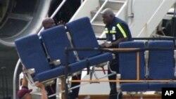Petugas tengah mengangkut kursi dari sebuah pesawat American Airlines 757 milik maskapai penerbangan AS, American Airlines, di bandara internasional Logan, Boston (2/10).