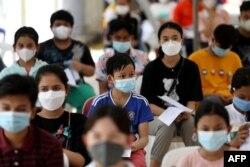 Para remaja menunggu untuk menerima vaksin Sinovac di sebuah pusat kesehatan di Phnom Penh pada 1 Agustus 2021, saat Kamboja mulai memvaksinasi remaja berusia antara 12 hingga 17 tahun. (Foto: AFP/Pring Samrang)