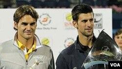 Novak Djokovic (kanan) dan Roger Federer (kiri) memegang trofi mereka setelah partai final Kejuaraan ATP Dubai bulan lalu. Keduanya akan ikut pertandingan sepak bola amal bagi upaya pemulihan bencana Jepang.