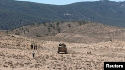 FILE - Tunisian soldiers patrol near Mount Chaambi in Kasserine region near the border with Algeria.