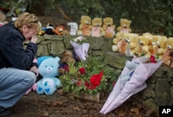 FILE - Cheryl Girardi, of Middletown, Conn., kneels beside 26 teddy bears, each representing a victim of the Sandy Hook Elementary School shooting, at a sidewalk memorial, Dec. 16, 2012, in Newtown, Conn.