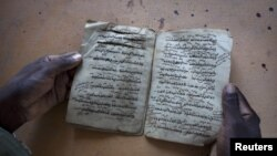 Aboubakar Yaro, head of conservation at the Djenne Library of Manuscipts, holds an Islamic manuscript from the 15th century, September 1, 2012.