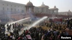 Polisi berupaya mengendalikan massa di depan istana kepresidenan di New Delhi dengan mempergunakan gas air mata dan meriam air (22/12). (Reuters/Adnan Abidi)