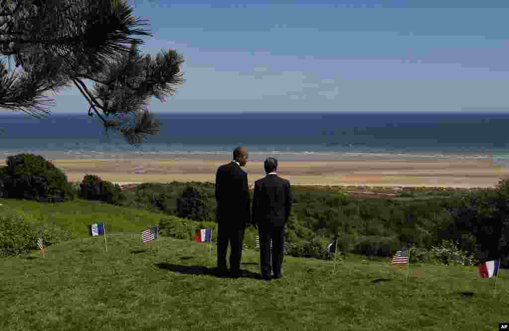 U.S. President Barack Obama and French President Francois Hollande look out at Omaha Beach, one of the sites of the Allied beach landings, at Normandy American Cemetery in Colleville sur Mer in Normandy, France, June 6, 2014.