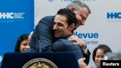 Walikota New York Mayor Bill de Blasio (kiri) memeluk bekas pasien ebola, dokter Craig Spencer setelah dinyatakan sembuh dan diperbolehkan meninggalkan rumah sakit Bellevue di New York, Selasa (11/11).