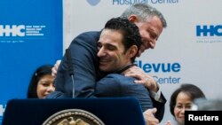 New York Mayor Bill de Blasio hugs Dr. Craig Spencer as he is discharged from Bellevue Hospital, after being stricken by Ebola, in New York Nov. 11, 2014.