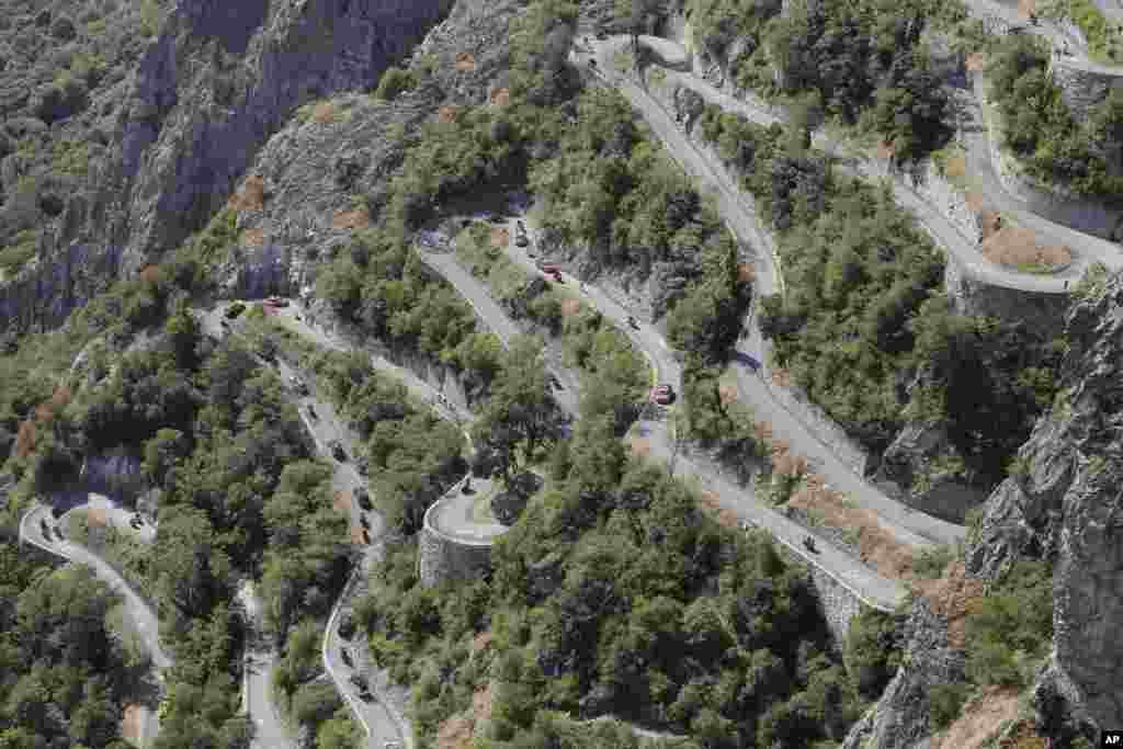 Riders, team cars and press motorcycles climb the hairpins of Montvernier during the eighteenth stage of the Tour de France cycling race over 186.5 kilometers (115.9 miles) with start in Gap and finish in Saint-Jean-de-Maurienne, France.