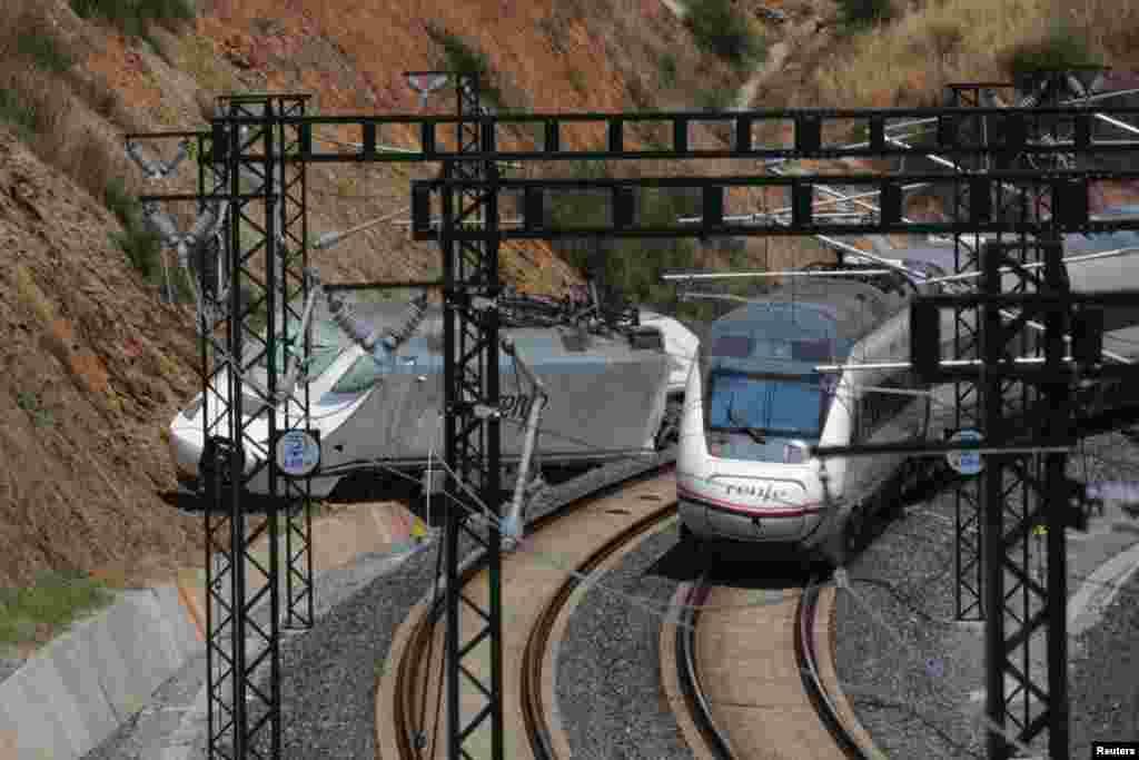 Un tren de pasajeros pasa junto a la máquina del tren accidentado el miédrcoles 24 de julio cerca de Santiago de Compostela, España, con un saldo de 79 muertos y varios heridos graves.