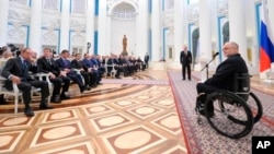 FILE - Sir Philip Craven, president of the International Paralympic Committee, right, speaks as Russian President Vladimir Putin, standing background center, listens to him during an awards ceremony in the Kremlin in Moscow, March 24, 2014.