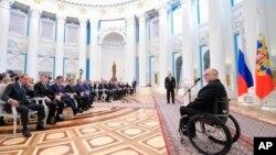 Sir Philip Craven, président du comité paralympique parle avec le président Vladimir Poutine, le 24 mars 2014.