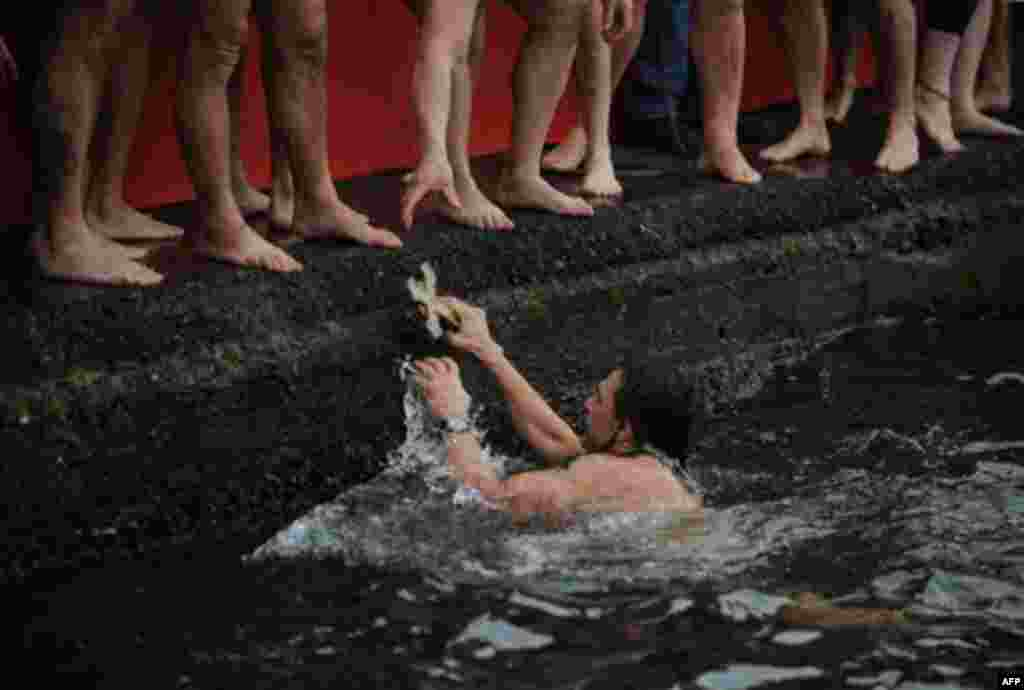 Greek Orthodox man Apostolis Oikomoniv holds the wooden cross after he retrieved it from the water during an Epiphany ceremony to bless the water in the Golden Horn in Istanbul, Turkey, Friday, Jan. 6, 2012. Similar ceremonies to mark Epiphany Day were h