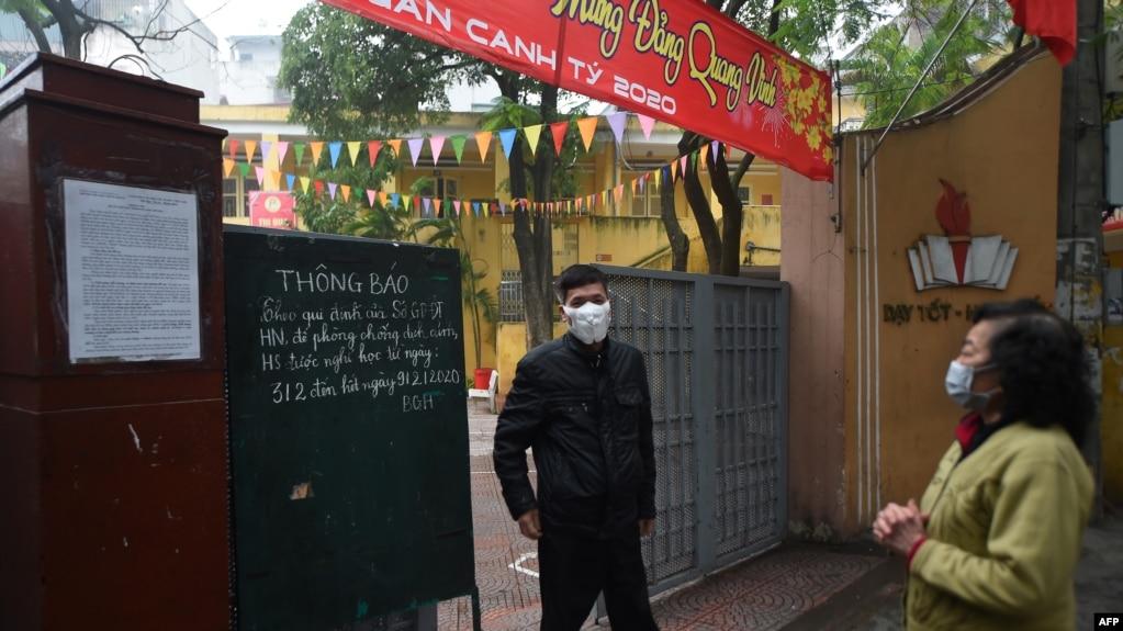 Một phụ huynh đọc thông báo trước cổng một trường tiểu học tạm thời đóng cửa để đề phòng sự lây lan của virus corona ngày 03/2/2020 ở Hà Nội