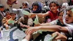Yemeníes muestran sus tarjetas de identificación para poder recibir alimentos de una organización caritativa en Sanaa, Yemen, en abril de 2017.