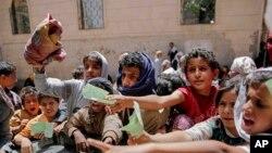 گروهی از کودکان یمنی در حال نشان دادن مدارک خود برای دریافت سهمیه غذا در صنعا پایتخت یمن - ۱۳ آوریل ۲۰۱۷