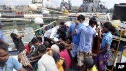 Foto yang dirilis tanggal 17 Oktober 2012 ini memperlihatkan para pencari suaka dari Sri Lanka tengah berupaya keluar dari kapal nelayan yang mereka tumpangi setelah tertangkap di sekata pangkalan angkatan laut di Galle, Sri Lanka. (AP Photo/Sajeewa Wijeweera). Sebuah kapal yang mengangkut 22 pencari suaka asal Sri Lanka, dilaporkan terdampar di dekat pulau Nusakambangan, Selasa (29/1).