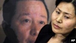 高智晟的妻子耿和在美国国会山参加一个新闻发布会时站在丈夫的画像前。(资料照片)