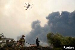 Petugas pemadam kebakaran mencoba memadamkan api kebakaran di dekat desa Afidnes, utara Athena, Yunani, 6 Agustus 2021. (REUTERS/Alexandros Avramidis/File Foto)