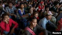 Cambodian workers wait for their documents to be processed at the Aranyaprathet police station as they prepare to move back to Cambodia, in Sa Kaew, Thailand, June 15, 2014.