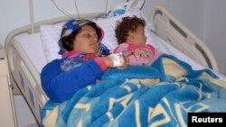 Una mujer y su hija heridas en lo que se cree fue un ataque con armas químicas son atendidas en un hospital de Siria.